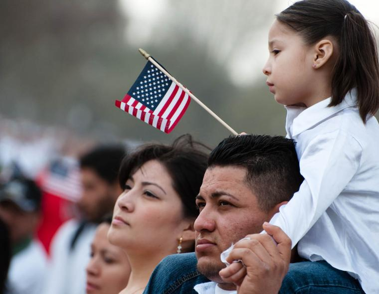 woman and man with girl on man's shoulders holding small american flag