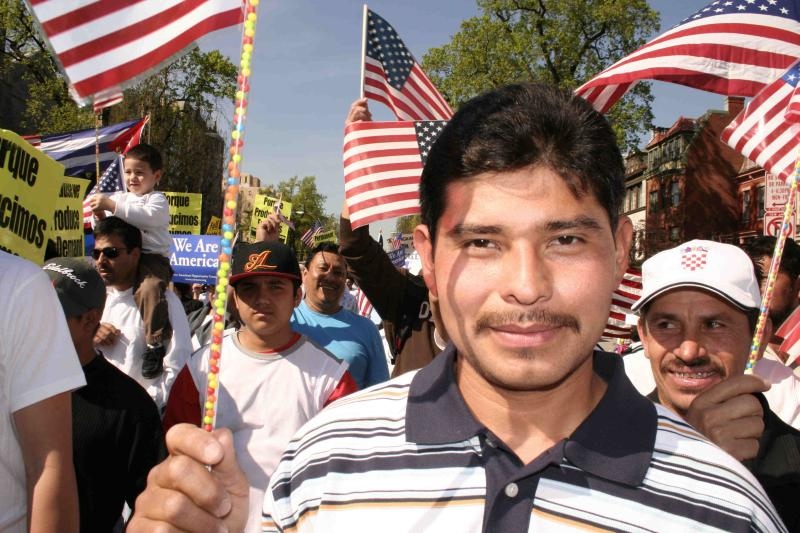 Immigrant rights demonstration with young man carrying American flag