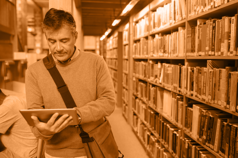 man in library stacks