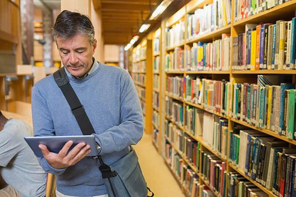 white man next to library shelves looking at ipad