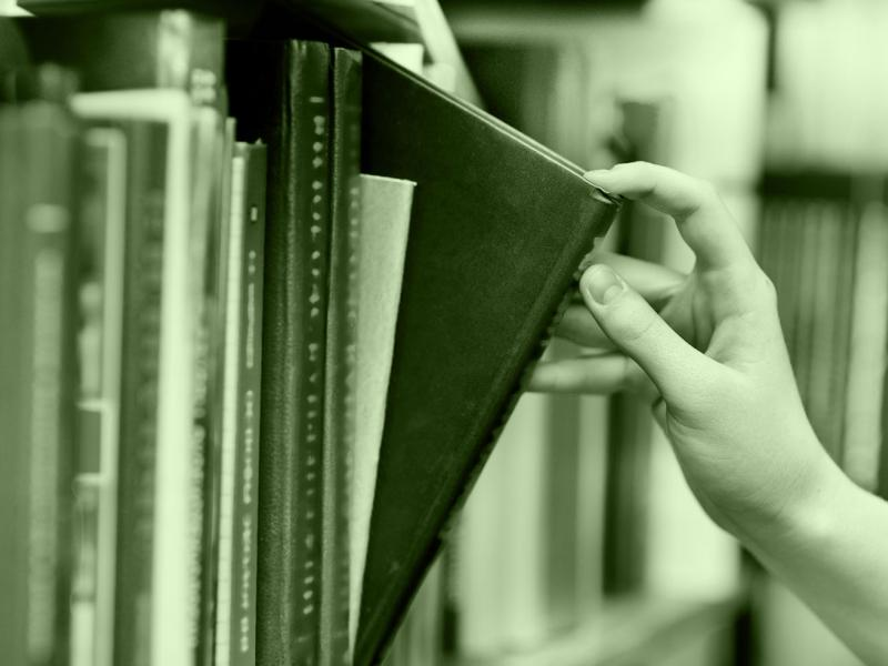 hand reaching for book on shelf