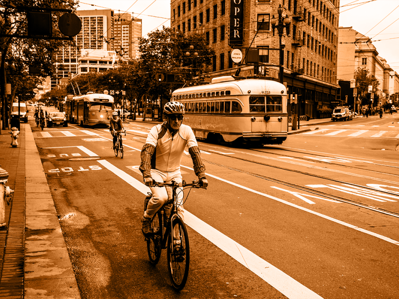 adult bike rider with streetcars in background